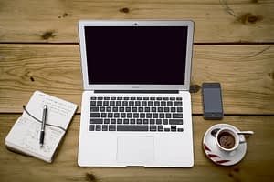 Translations on computer with phone and coffee